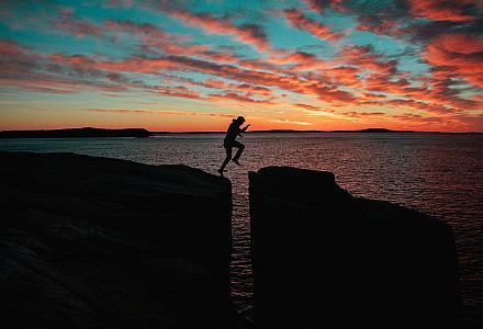 Challenge: Person springt im Abendlicht über eine tiefe Schlucht