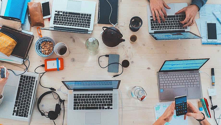 Schreibtisch voller Laptops, Tablets und Smartphones