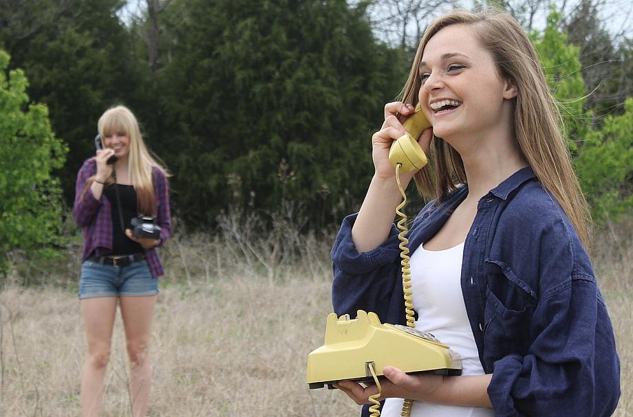 Zwei Jugendliche halten antike Telefone in den Händen.