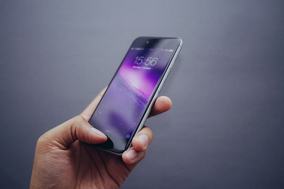 Mensch hält ein Smartphone in der Hand, das die Uhrzeit anzeigt.