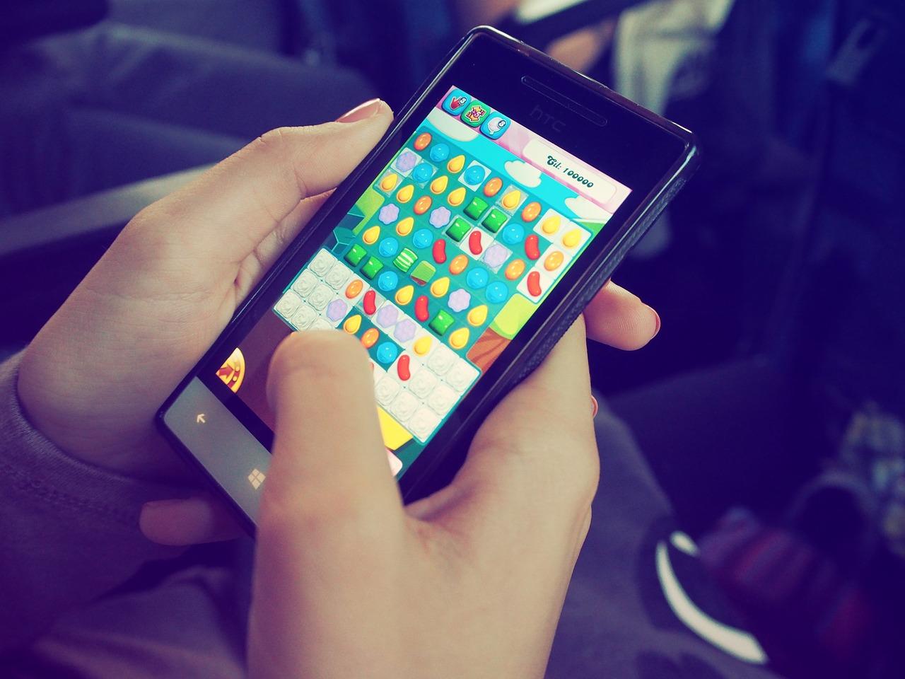 Auf einem Smartphone wird das Spiel Candy Crush gespielt, das mobile Game lässt sich auch leicht während der Arbeitszeit spielen