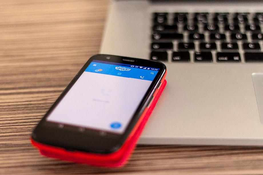 Ein Smartphone liegt auf der Tastatur eines Laptops