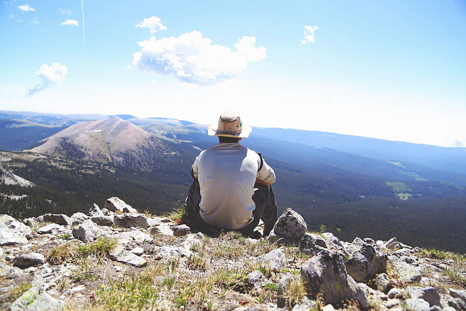Mann mit Hut sitzt auf einem Berg und schaut ins Tal hinab.