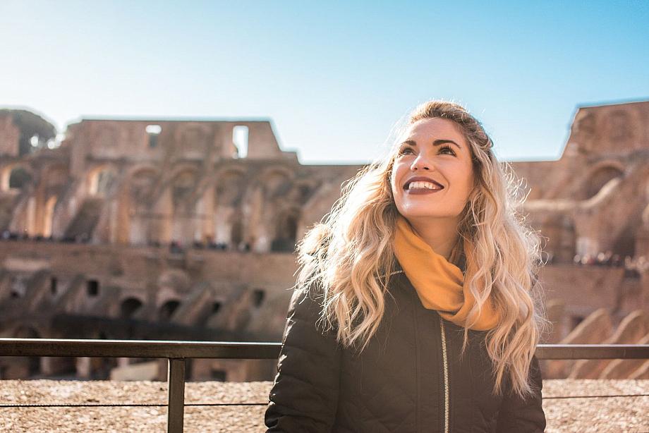 Frau steht in mitten einer Ruine aus der römischen oder griechischen Antike