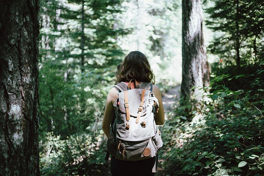 Frau mit Rucksack wandert durch den Wald