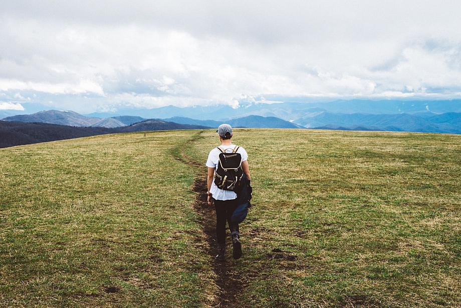 Mann wandert durch eine weite Graslandschaft