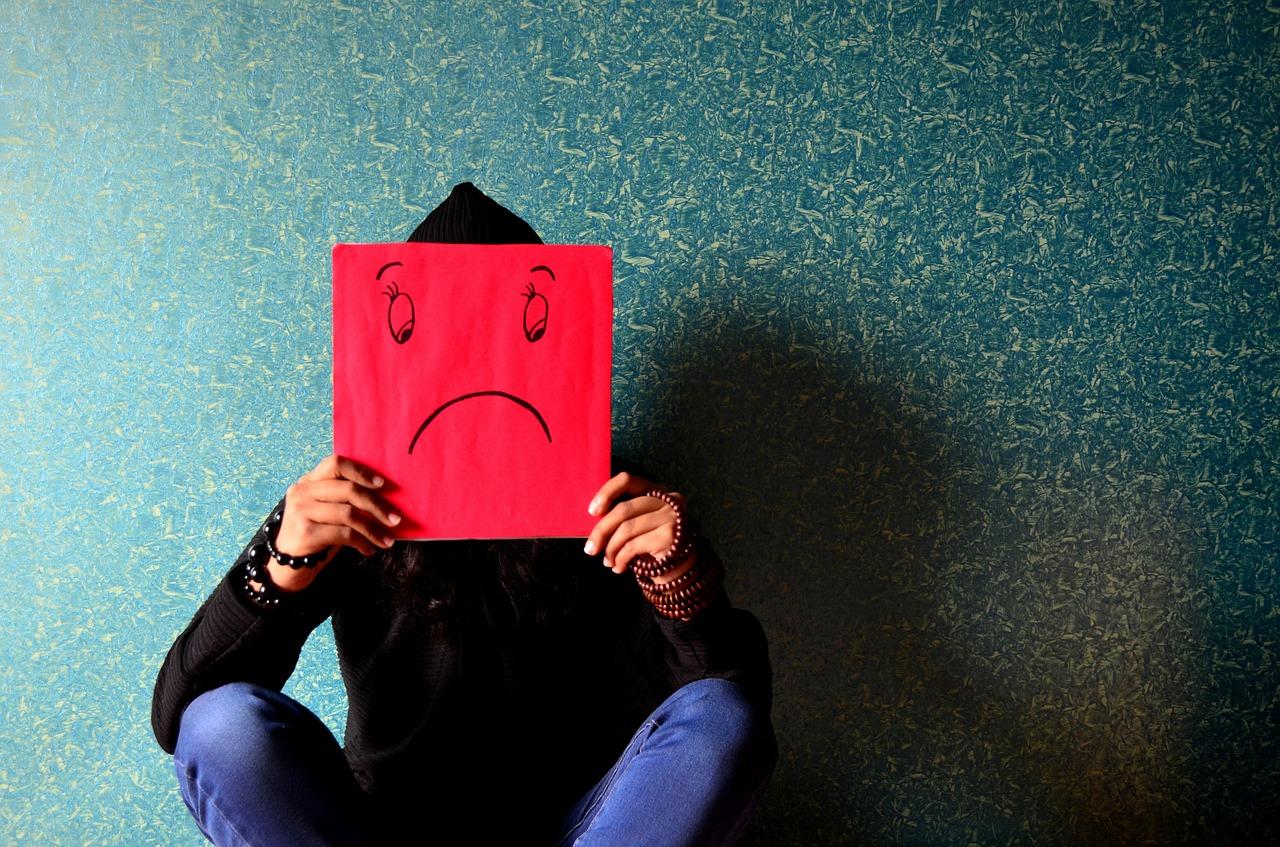 Person hockt auf dem Boden an die Wand gelehnt und hält sich ein rotes Schild vors Gesicht, auf dem ein trauriger Smiley zu sehen ist.