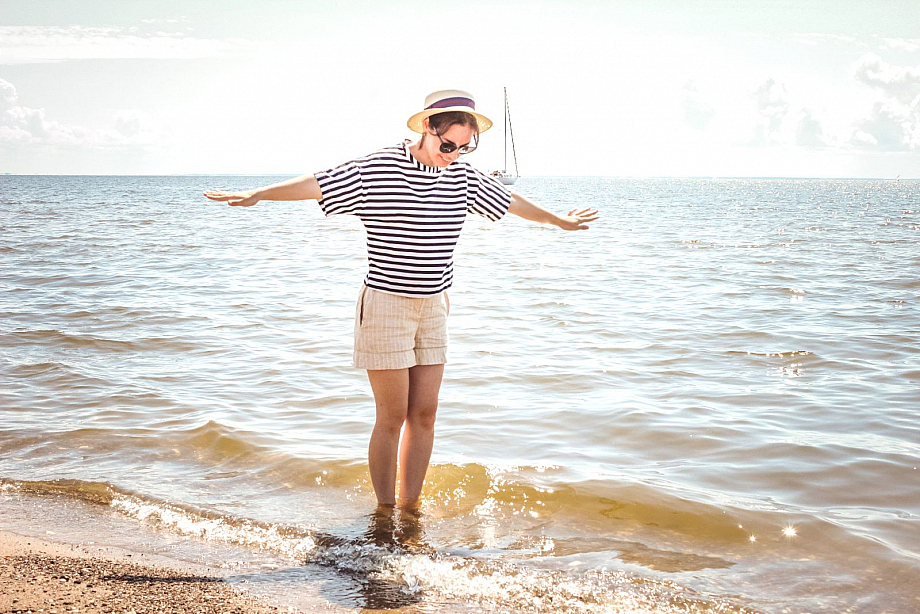 Frau tanzt am Strand in den Wellen