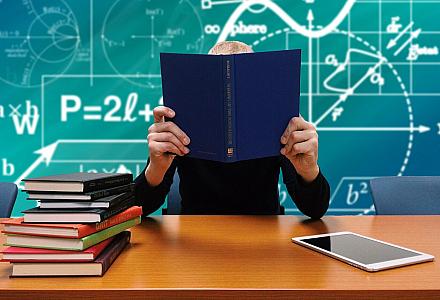 Dozent hinter einem Tisch voll Bücher. Im Hintergrund eine Tafel mit vielen Formeln.