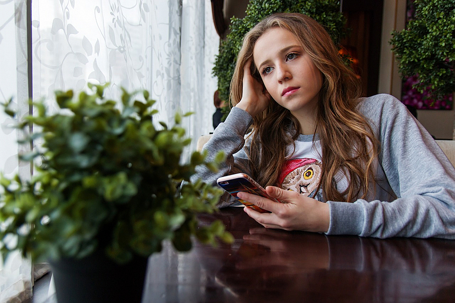 Mädchen sitzt alleine am Fenster mit Handy in der Hand