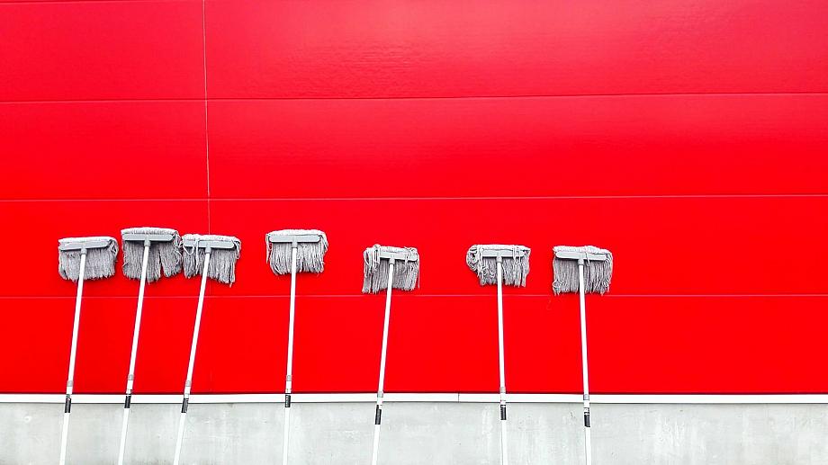 Sieben Wischmops stehen an einer roten Wand