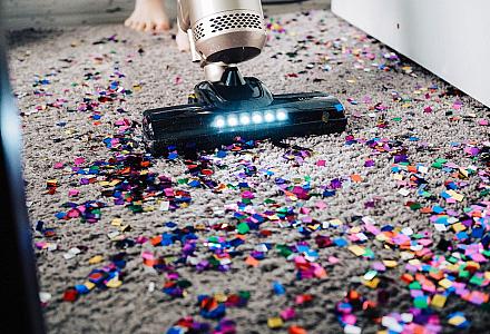 Staubsauger saugt Konfetti vom Teppich