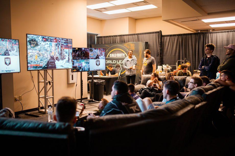 EIne Gruppe von Menschen sitz auf einem großen Sofa und guckt auf mehreren Bildschirmen einem eSport Wettkampf zu