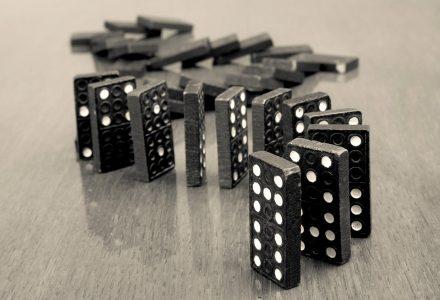 Dominosteine in einer Reihe aufgestellt, ein paar sind schon umgefallen, ein paar stehen noch.