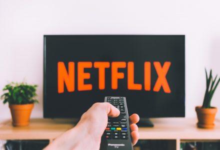 TV-Bildschirm mit Netflix-Logo im hintergrund. Im Vordergrund hält jemand eine Fernbedienung.