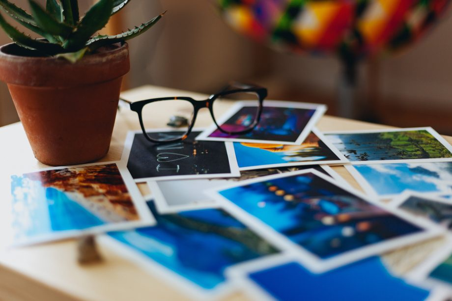 Viele Fotos auf einem Tisch, daben liegt eine Brille.