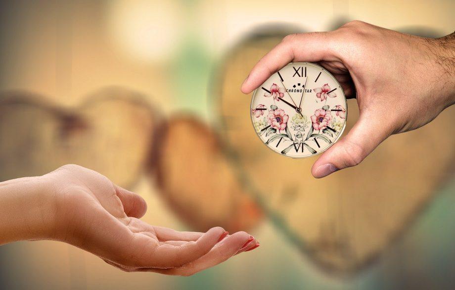 Zwei Hände. Die rechte Hand hält eine Uhr und gibt sie der linken Hand. Im Hintergrund erkennt man verschwommen Herzen aus Holz.