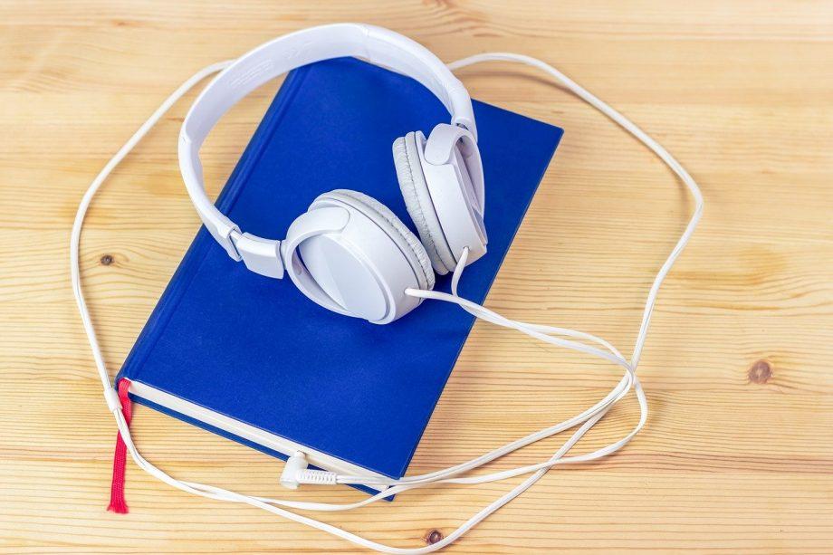 Auf einem Holztisch liegt ein blaues Buch mit rotem Lesezeichen. Auf dem Buchdeckel liegen große weiße Kopfhörer.