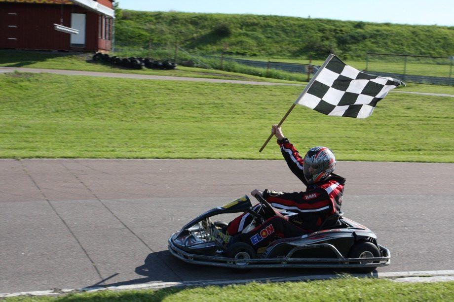 Ein*e Kartfahrer*in fährt mit der Zielflagge in der Hand.