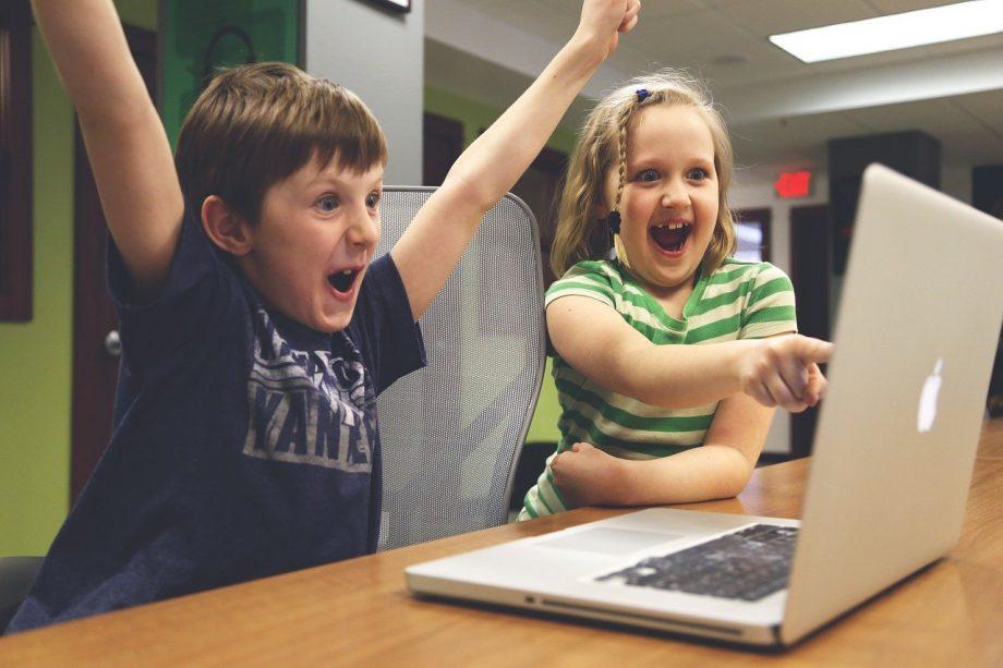 Zwei Kinder sitzen vorm Computer und freuen sich.