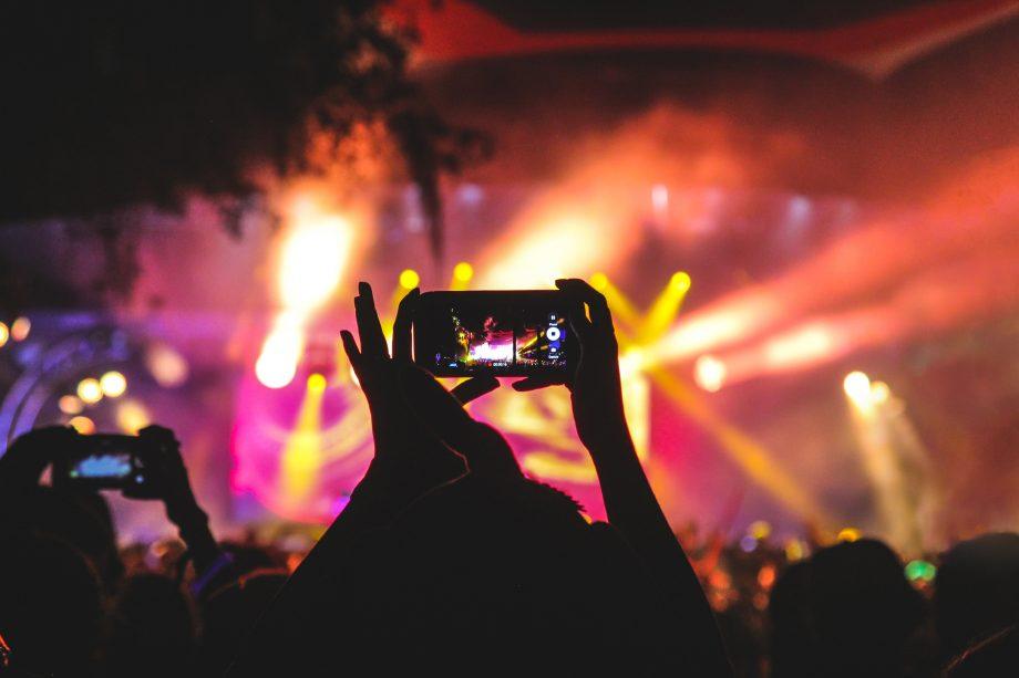 Auf einem Konzert wird ein Smartphone hochgehalten, um Fotos und Videos zu machen.