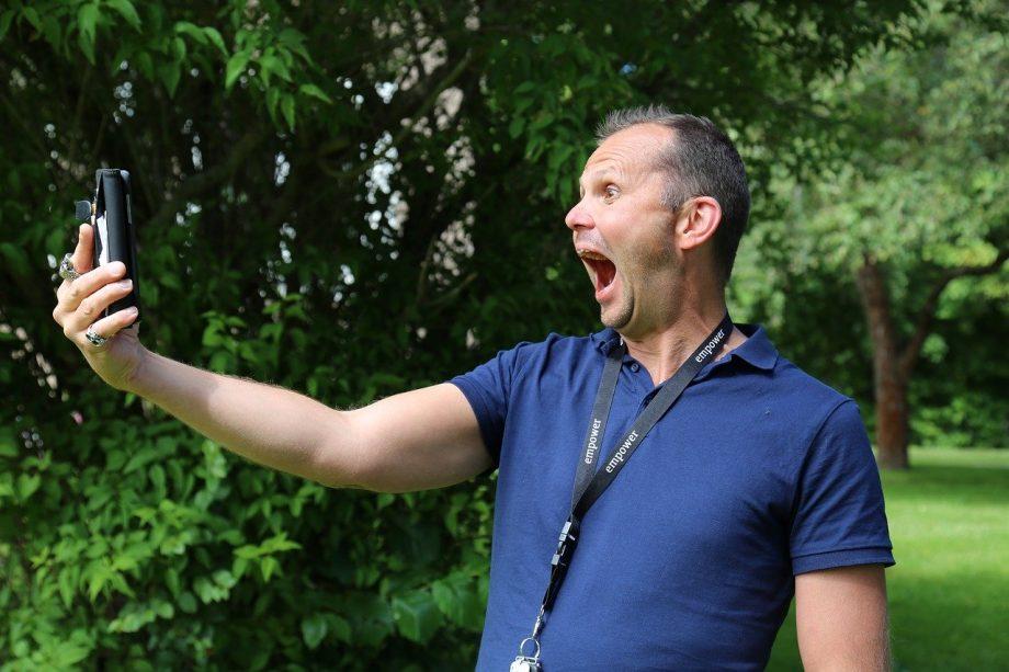 Ein Mann steht in einem Park. Er hält sein Handy mit dem rechten Arm weit von sich weg. Seine Augen und sein Mund sind weit aufgerissen.