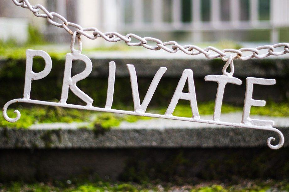 """Buchstaben aus Metall ergeben das englische Wort """"private"""" und hängen an einem Durchgang"""