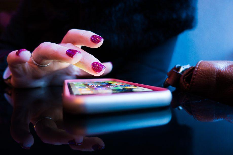 Frau mit bunten Fingernägeln tippt auf ein Smartphone, das auf einem Tishc liegt.