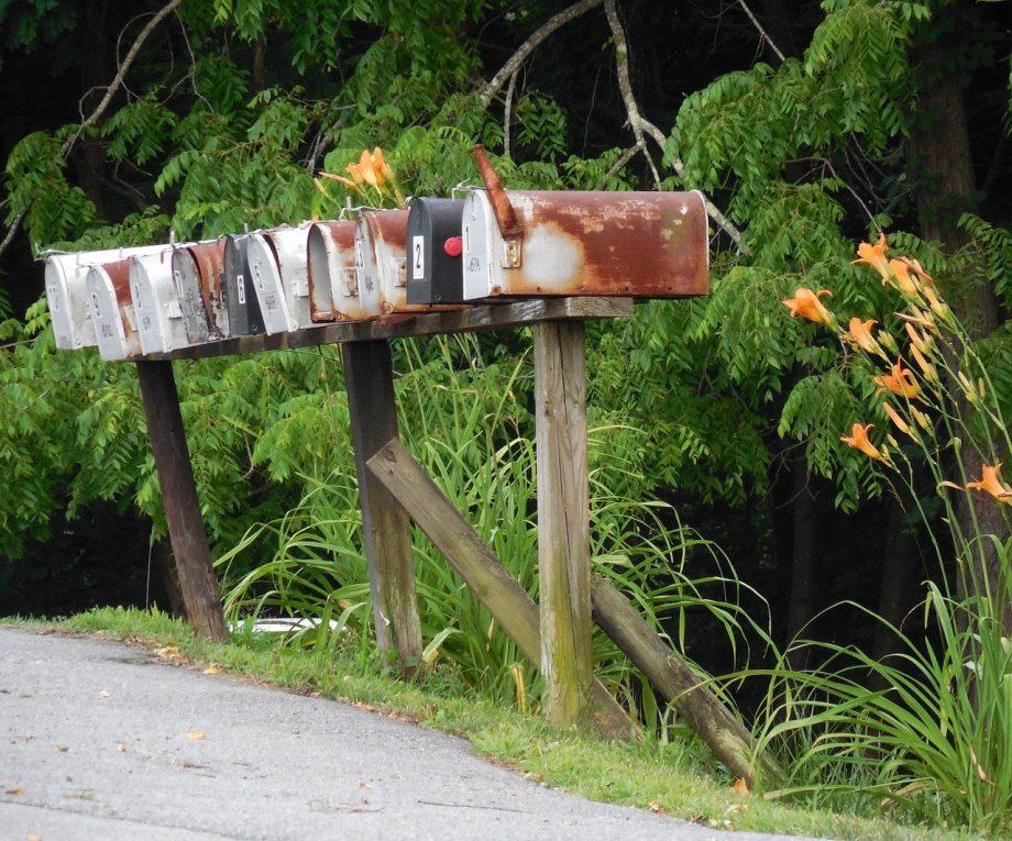 Viele Briefkästen nebeneinander am Wegesrand