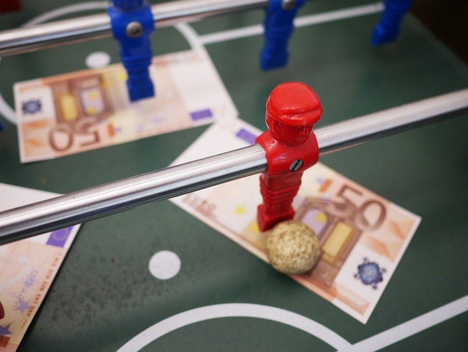 Tischkicker in der Nahaufnahme. Man sieht eine rote SPielfigur mit einem goldenen Ball vor den Füßen. Auf dem Spielfeld liegen 50-Euro-Scheine.