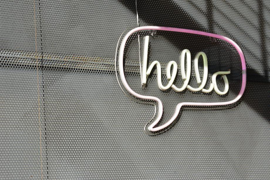"""Wand aus Beton. Daran eine Leuchtreklame in Form einer Sprechblase. In der Sprechblase steht """"Hallo""""."""