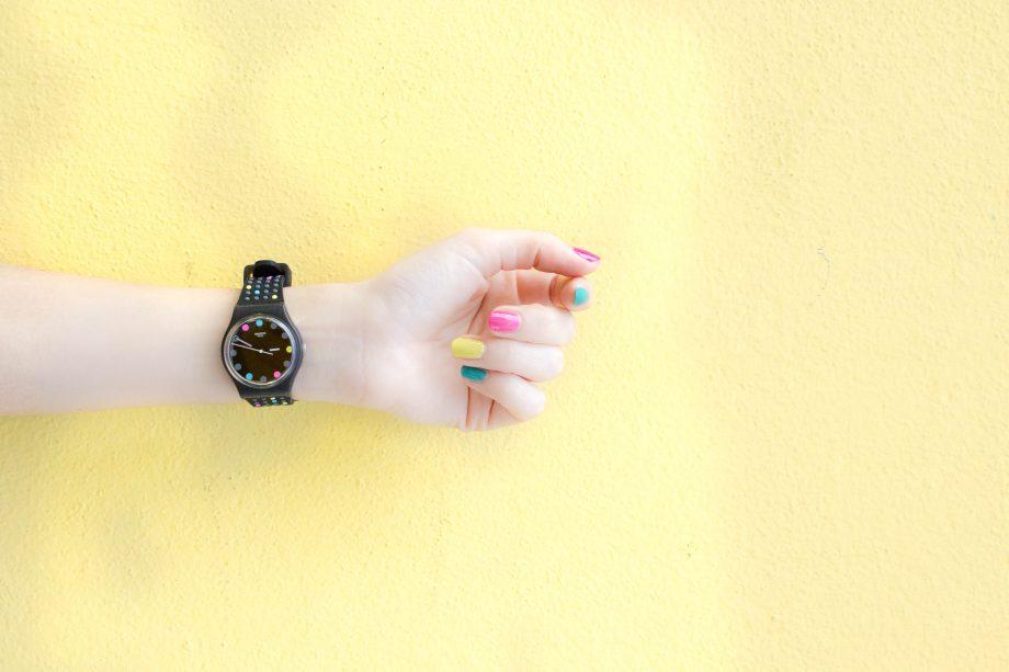 Ein Arm mit einer bunten Uhr und bunten Fingernägeln.