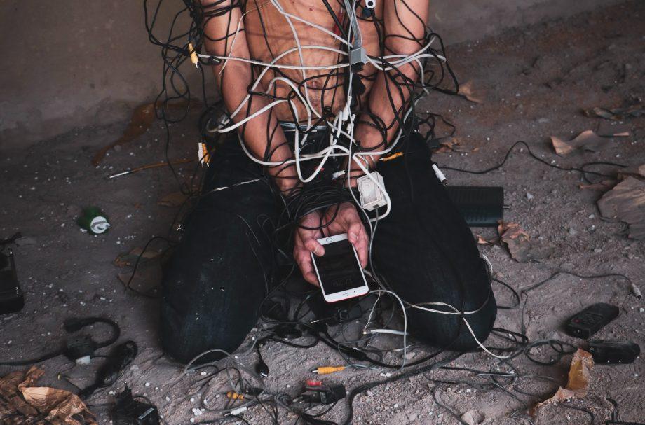 Person ist mit Kabeln gefesselt und hält ein Smartphone in den Händen