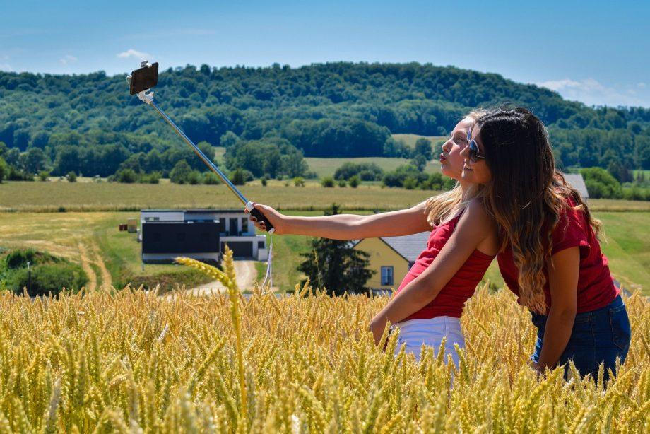 Zwei Frauen machen ein Selfie im Kornfeld.