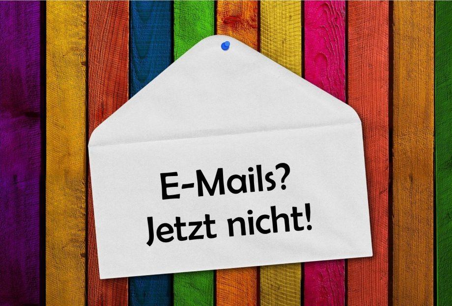 """Bunt gestreifter Hintergrund, an den ein Briefumschlag gepinnt ist. Auf dem Umschlag steht: """"E-Mails? Jetzt nicht!"""""""