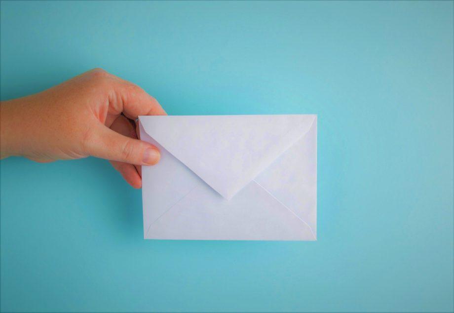 Hellblauer Hintergrund. Von links kommt eine Hand ins Bild, die einen leeren Briefumschlag hält.