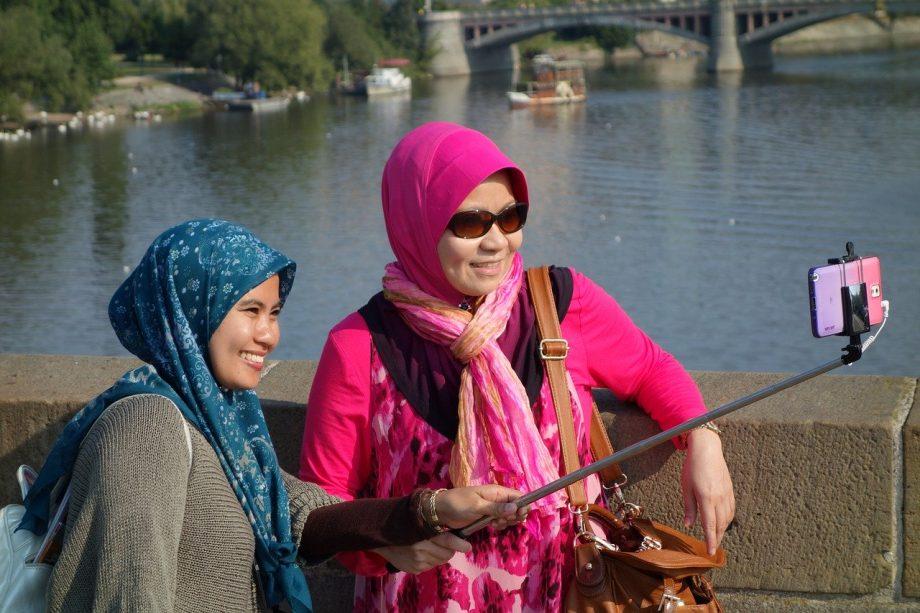 Zwei Frauen machen ein Selfie von sich auf einer Brücke.