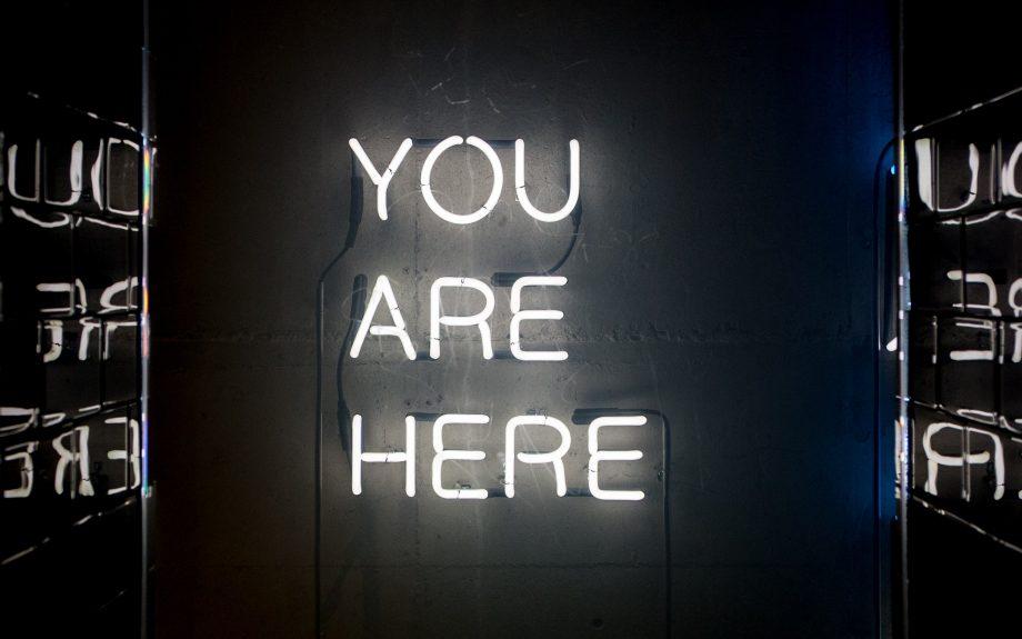 """Neon-Leuchtschrift titelt """"You are here"""", """"Du bist hier"""""""
