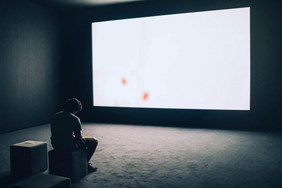 Person sitzt alleine in einem großen Raum mit riesigem Bildschirm an der Wand