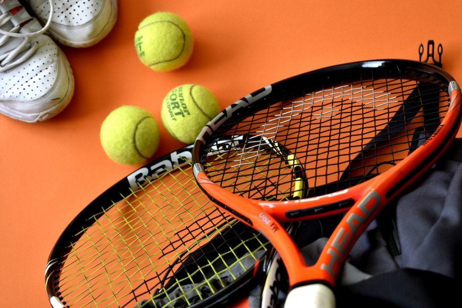 Tennisschläger, tennisbälle und Turnschuhe