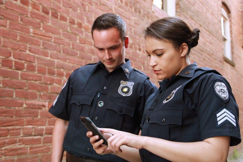 Polizist und Polizistin gucken gemeinsam auf ein Handy