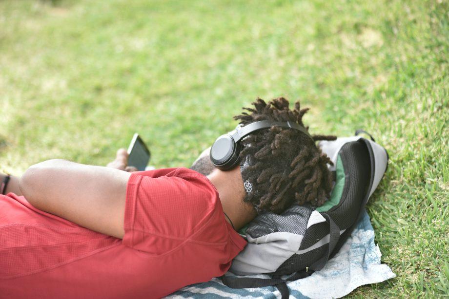 Mann im Park guckt auf sein Handy