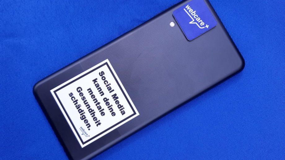 Handy mit Sticker und Reinigungspad